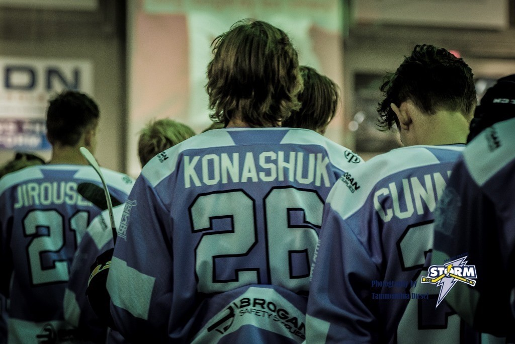 Hockey players walking away from the camera with their names and numbers visible on the backs of their jerseys
