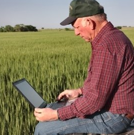 Image of farmer in field with laptop