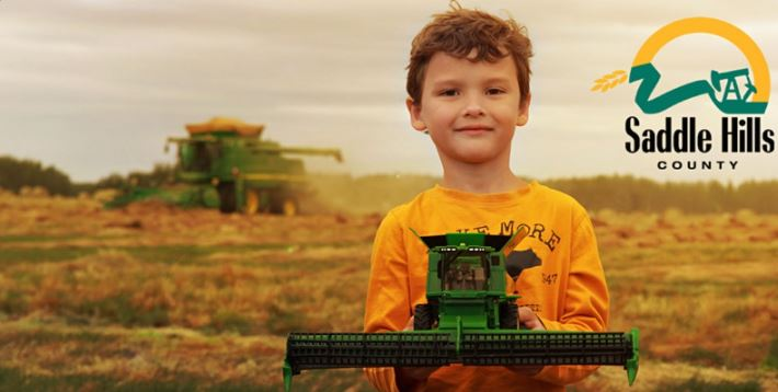 Image of boy holding combine in front of actuall combine in the field